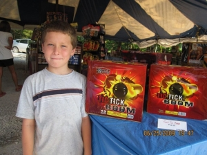 Ethan who helps his dad, Jason Napier, stands beside his favorite fireworks.