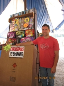 Jason Napier stands in front of a $300 display of fireworks that their family fireworks tent is giving away in a $1.00 per chance game.   Customers can put quarters in a gumball -like machine and instantly win everything from bouncy balls to fireworks, including the one featured in this photo.